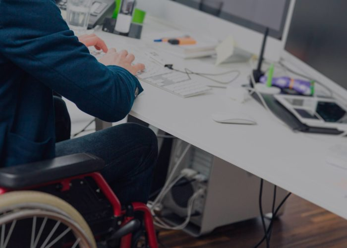 Disabled man at work in a wheelchair sitting at a desk using a computer