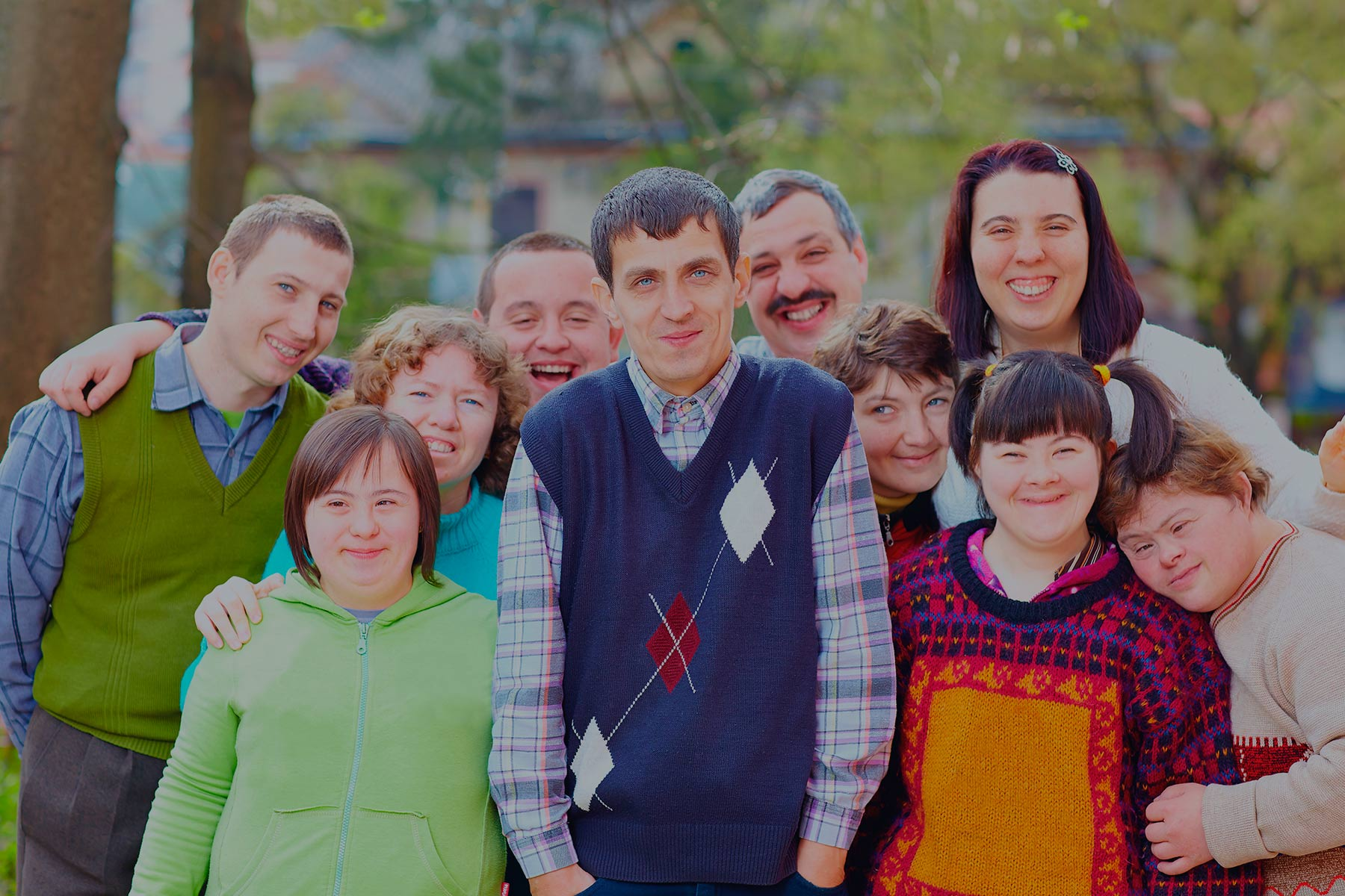 A group of smiling special needs children and adults