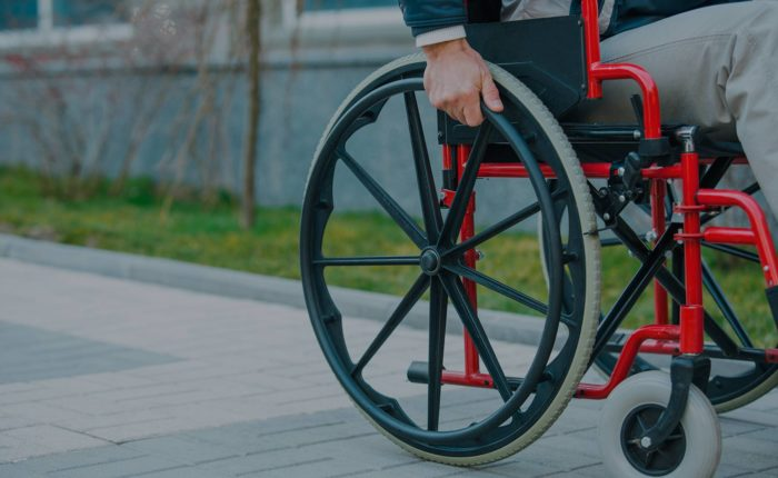 Man outside in wheelchair going down a path